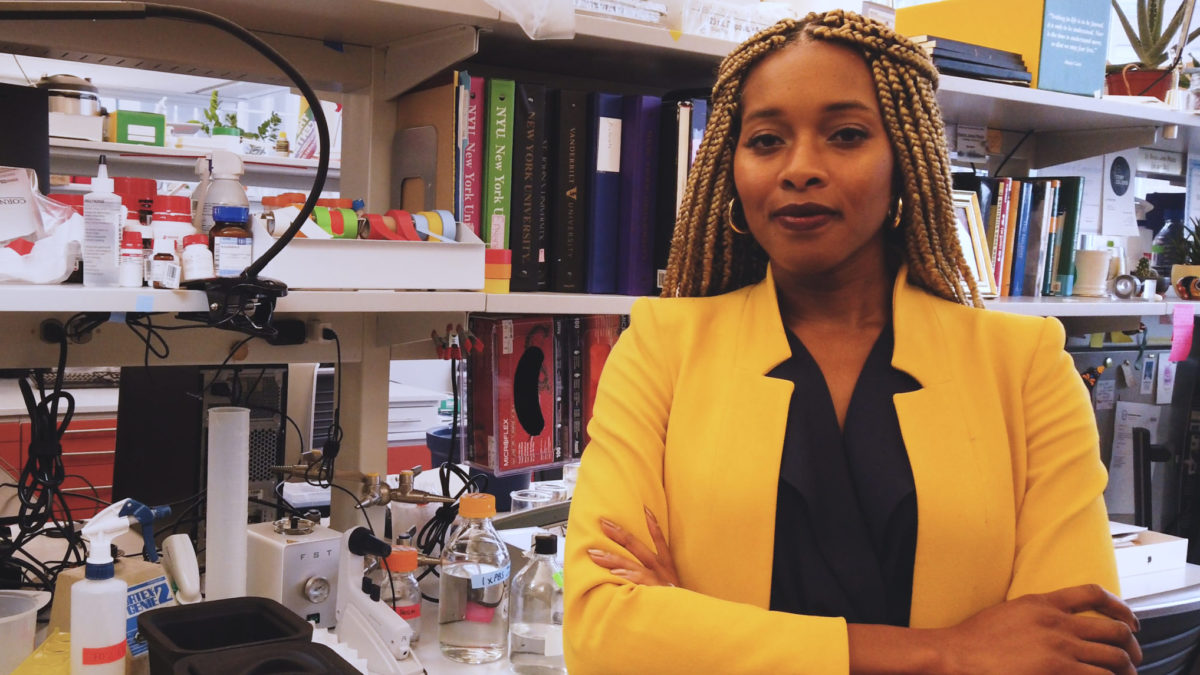 a black woman in a yellow coat poses in front of the camera in her lab