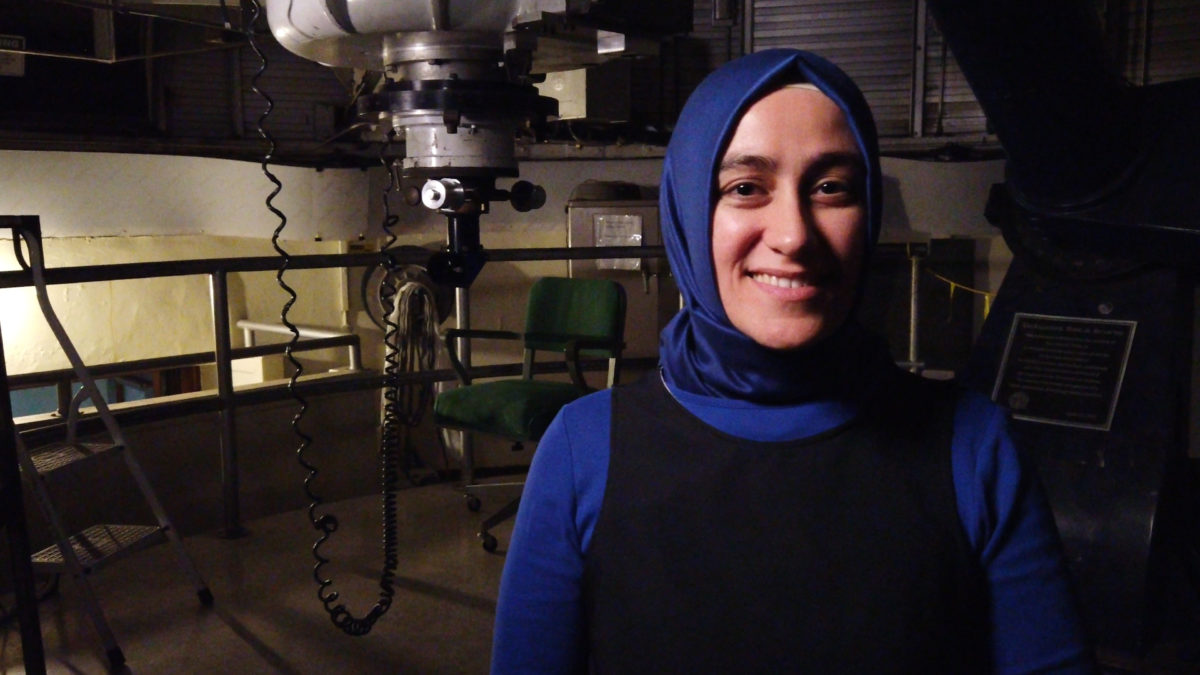 woman wearing headscarf smiles at camera with heavy electronics behind her