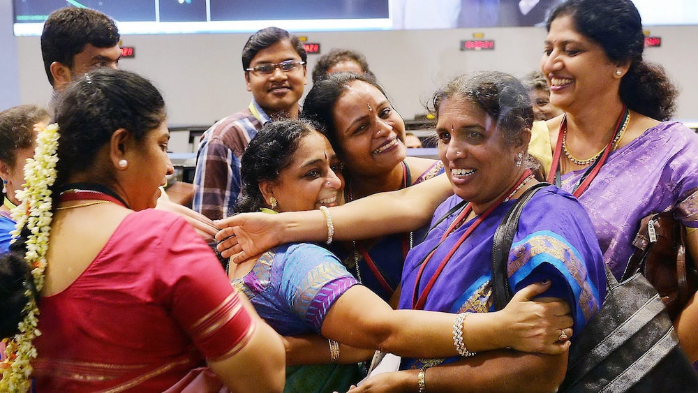 engineers of isro embracing after the successful launch of their mars satellite