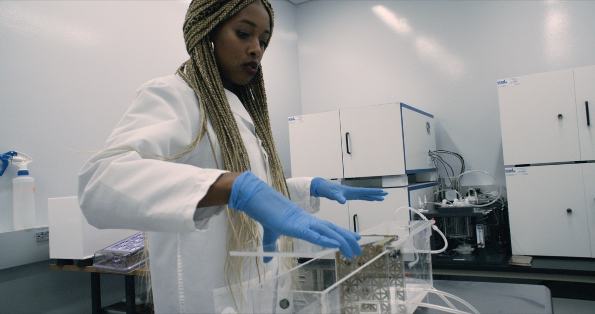 a black woman in a lab coat and gloves in a lab lifting the top of a clear container with experimental equipment