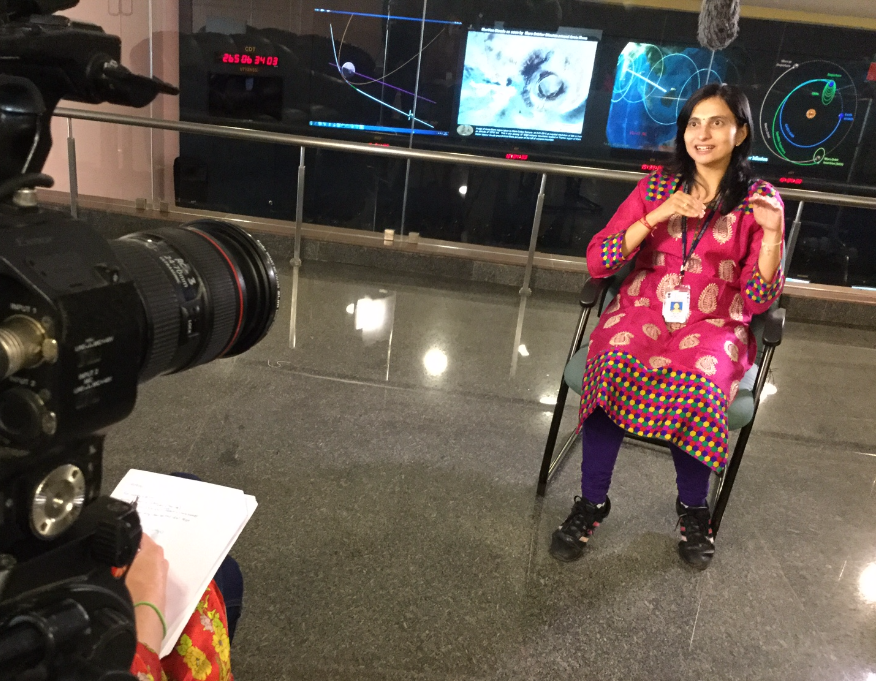a woman in a pink sari being interviewed in front of orbit schematics